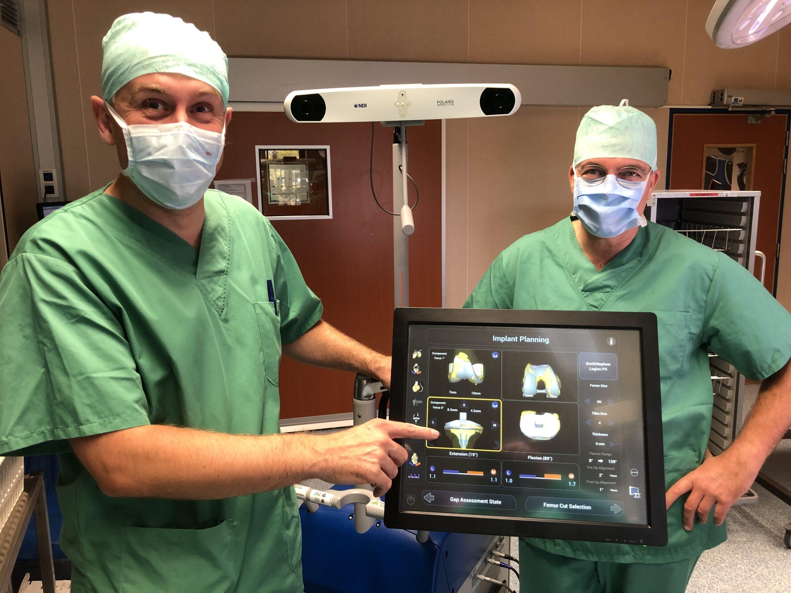 Dr. Tom Peeters (links) en Dr. Vincent Roosens (rechts) bij de Navio-robot.